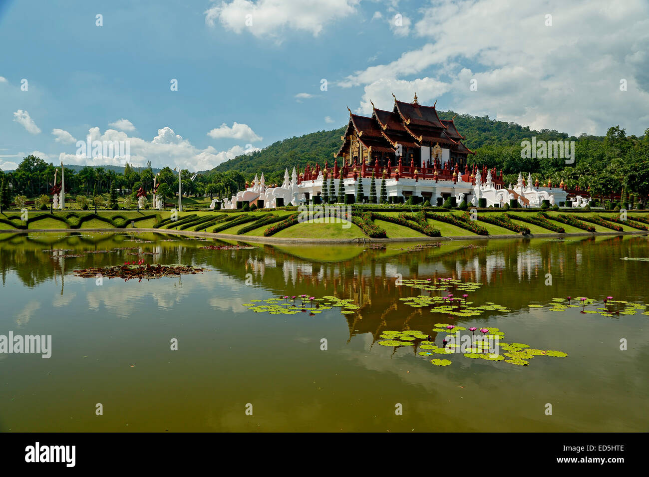 Royal Pavilion reflected on pond with lily pads, Royal Park Rajapruek, Chiang Mai, Thailand - Stock Image