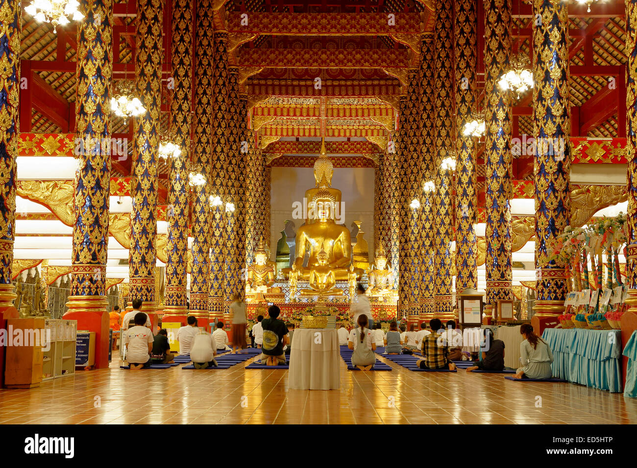 Buddha statue and worshipers, prayer hall, Wat Suan Dok, Chiang Mai, Thailand - Stock Image