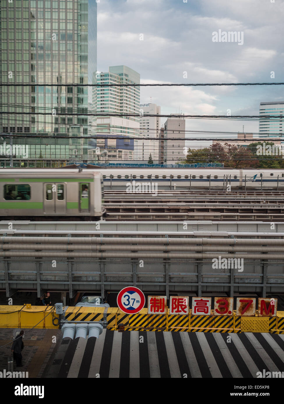 Train lines crossing over road with skyscrapers in background in Tokyo city Stock Photo