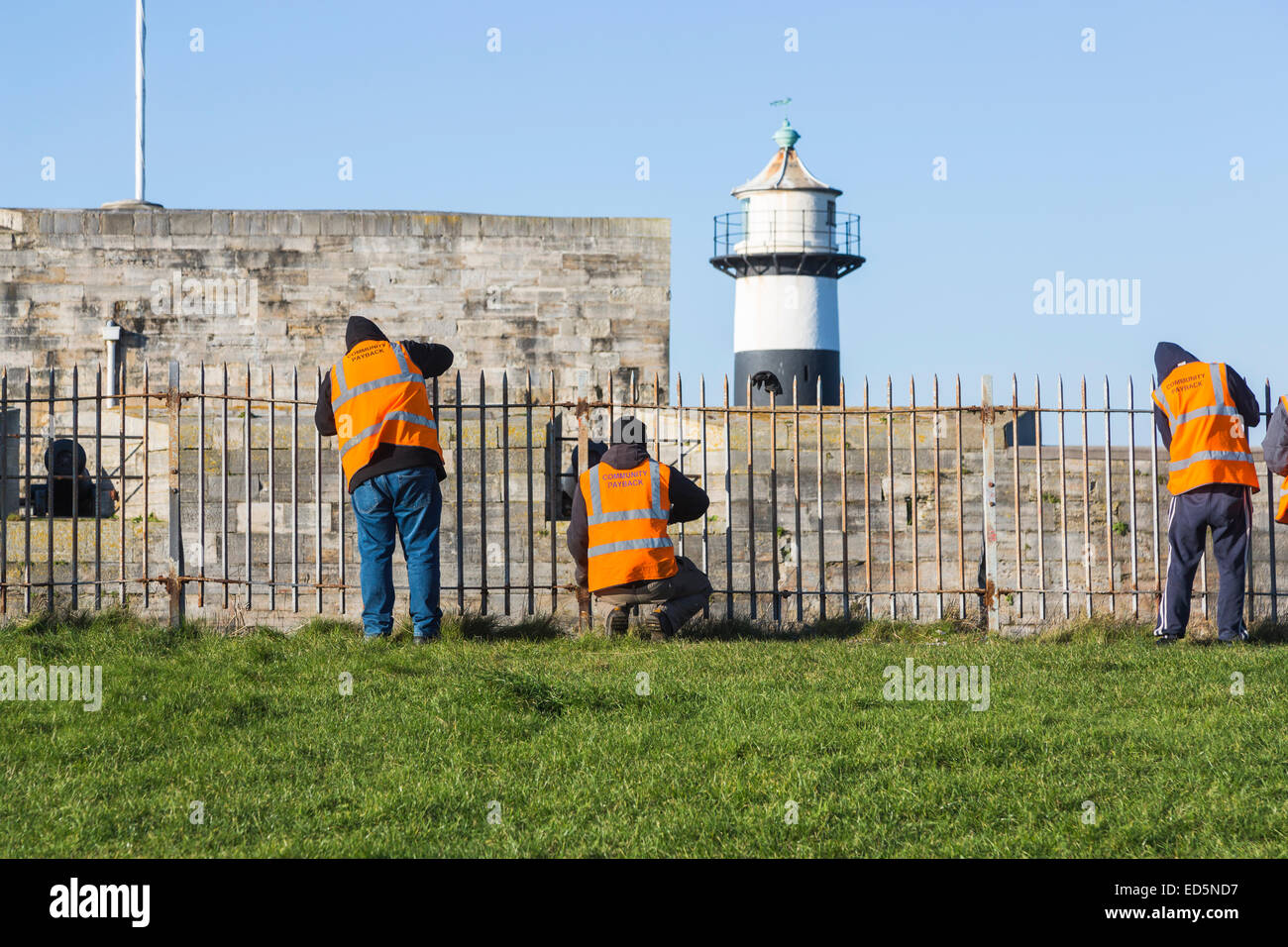 Offenders working at Southsea Castle, Portsmouth, carrying out community service; orange jackets inscribed 'Community - Stock Image