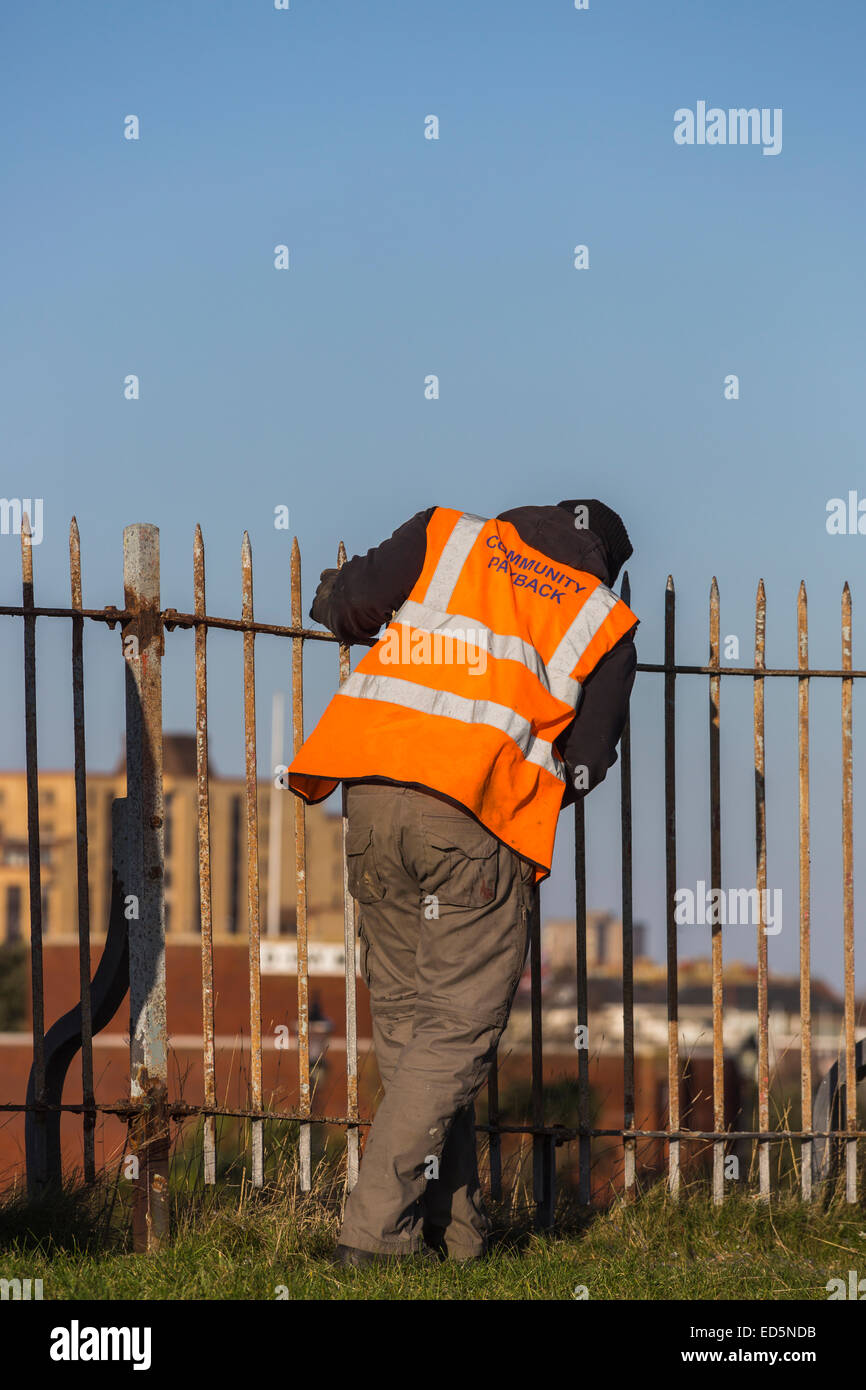 Offender working at Southsea Castle, Portsmouth, carrying out community service; orange jacket inscribed 'Community - Stock Image