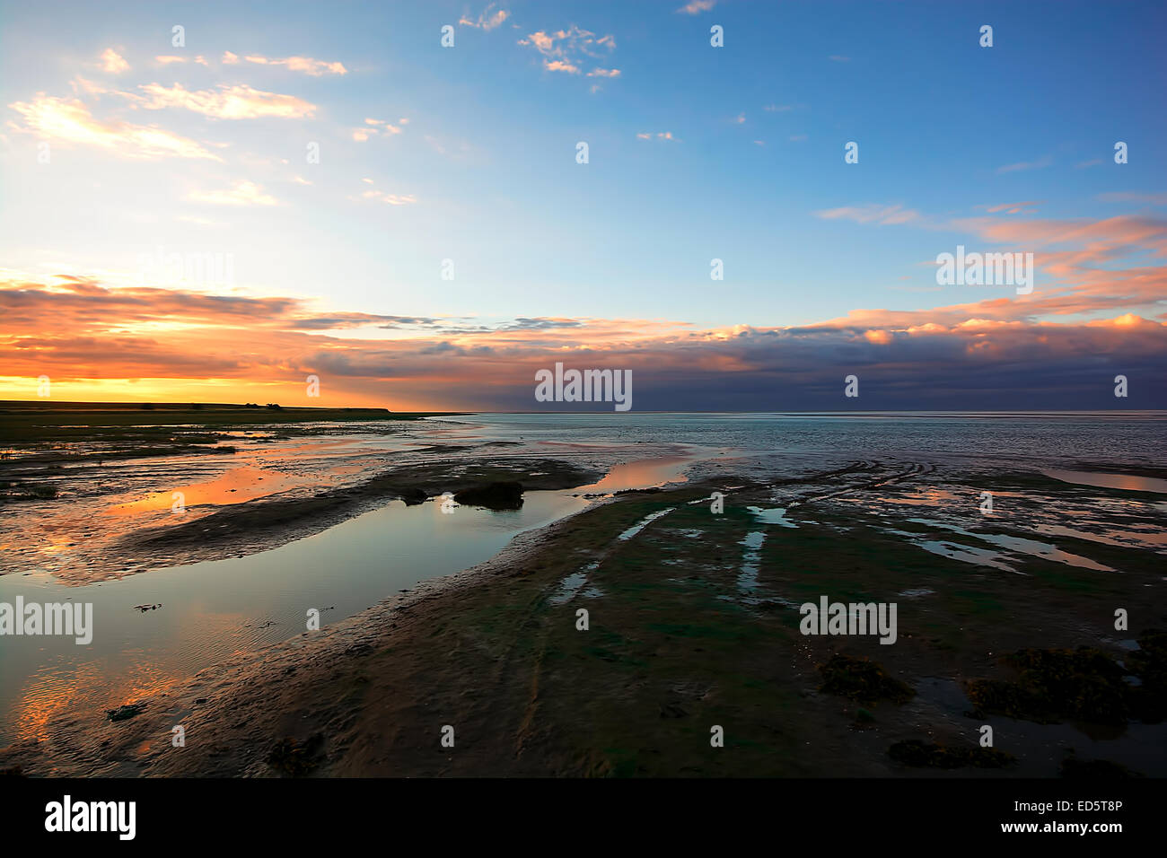 The sun setting over the north Northumberland coast as seen from Lindisfarne (Holy Island) causeway. Northumberland Stock Photo