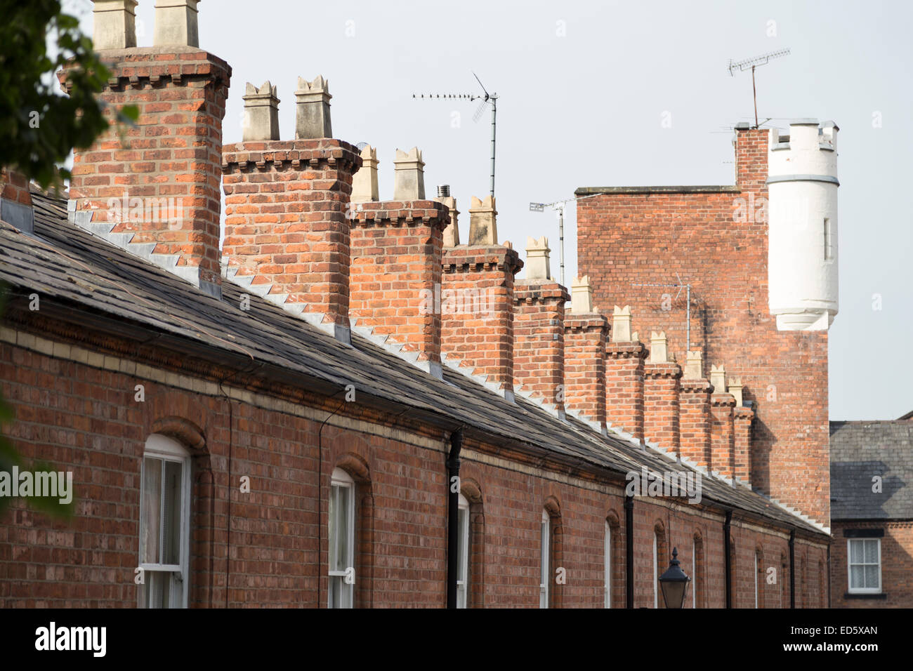 UK, Chester, a row of chimneys on houses with the last one looking like a castle turret. - Stock Image