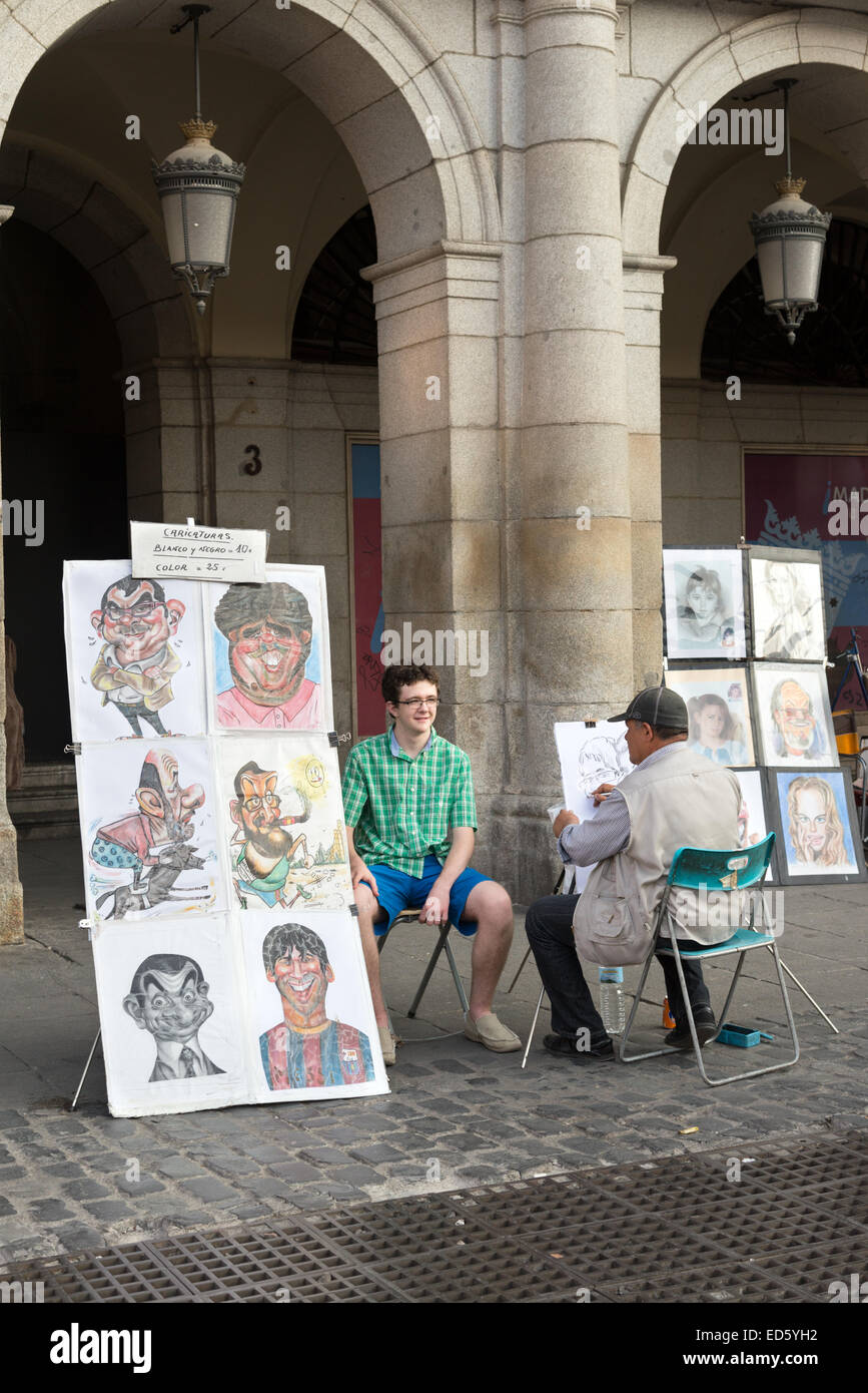 Caricaturist at work in the Plaza Mayor, Madrid, Spain - Stock Image