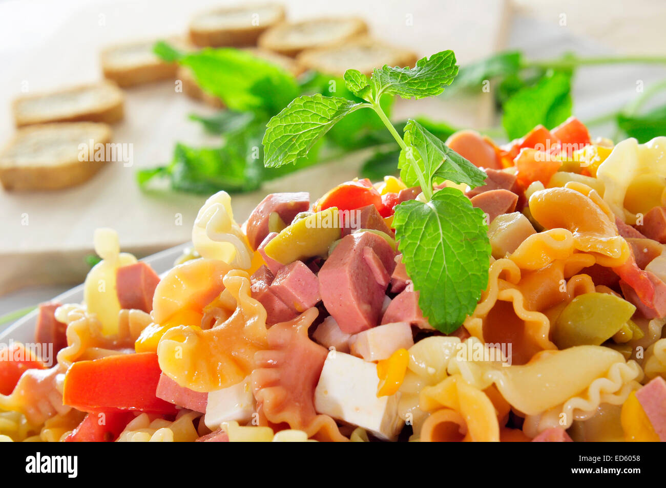 closeup of a refreshing pasta salad, with feta cheese, tomato, olives and frankfurter sausages - Stock Image