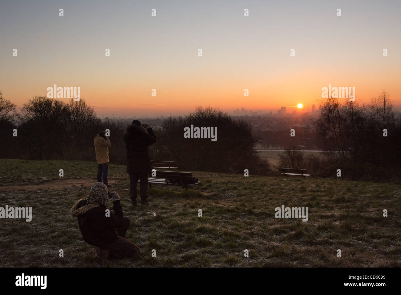 London UK, 29th December 2014. People photograph the view at sunrise on Parliament Hill as London wakes to a beautiful - Stock Image