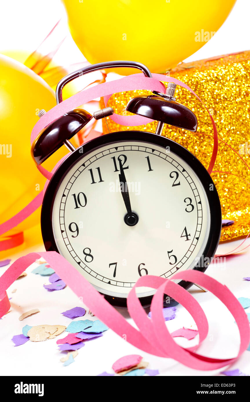a watch at twelve, balloons, a golden top hat, streamers and confetti for the new years party - Stock Image
