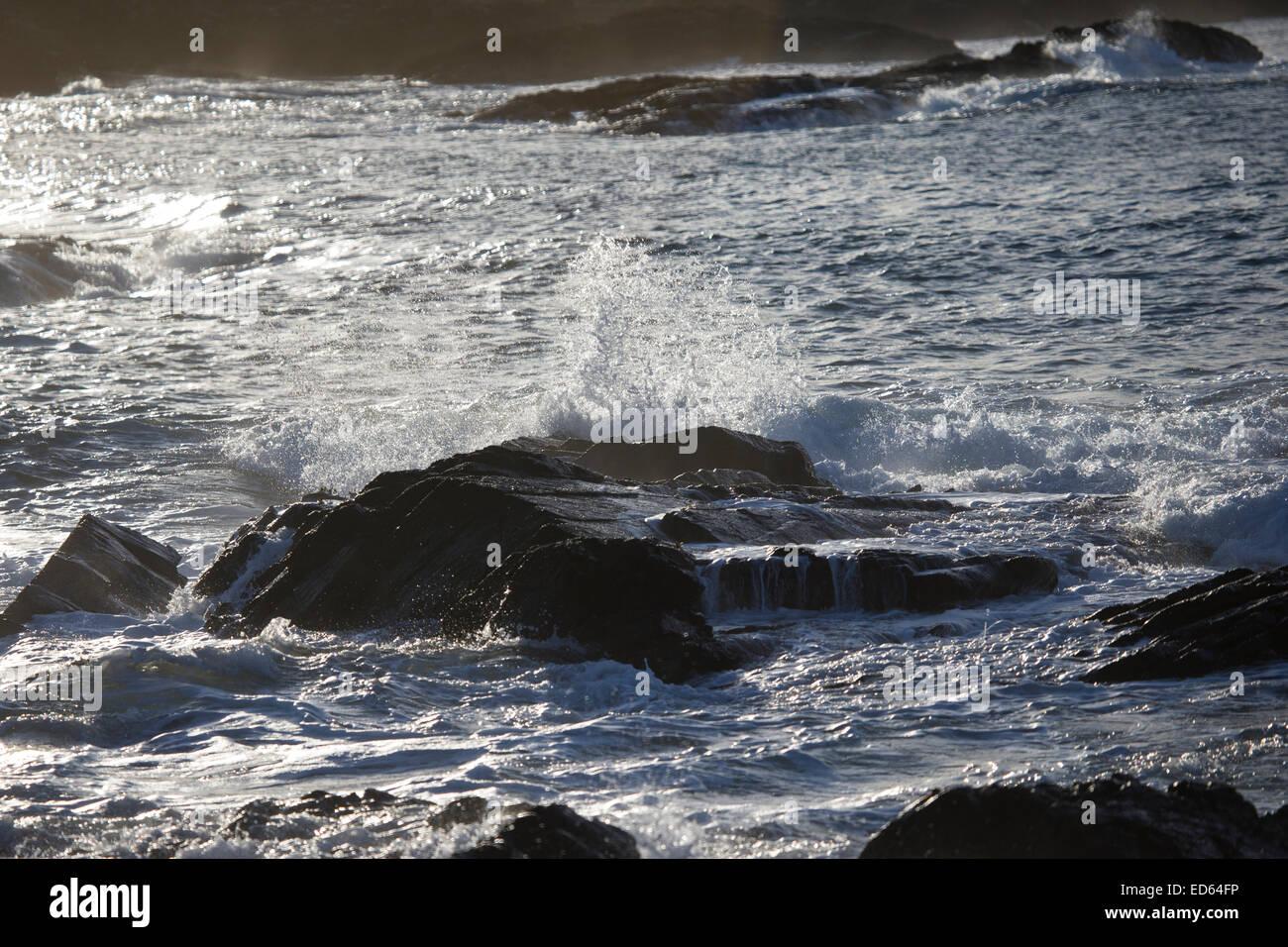Coastal waves backlit and breaking against the rugged rocks on the Scottish western coast - Stock Image