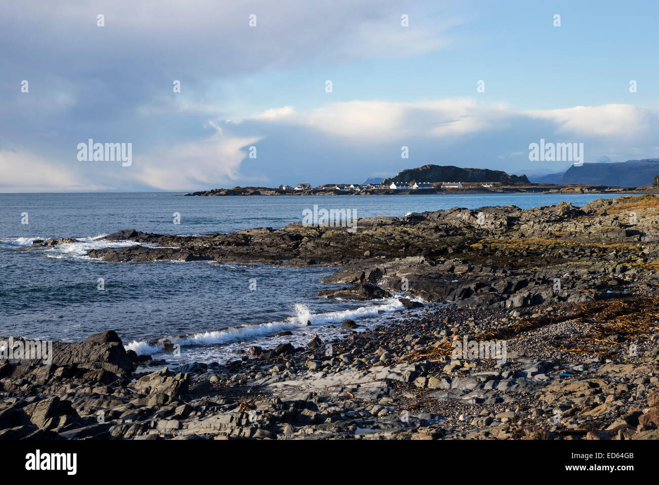 View of incoming tide and breakers on the rocky foreshore looking towards Ellenabeich on a brisk winter day in Scotland - Stock Image