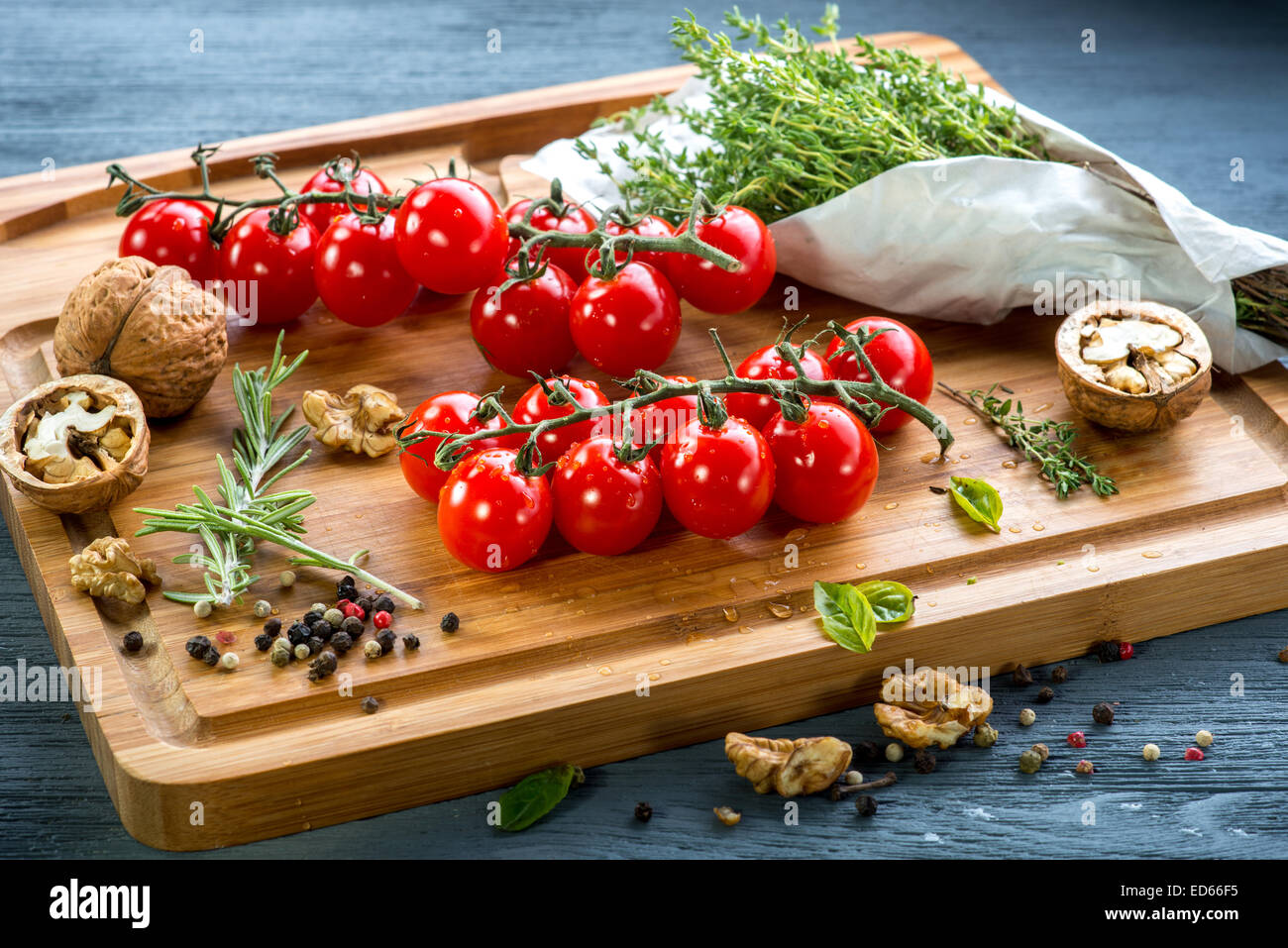 Tomatoes cherry with spices and nuts on wooden desk - Stock Image