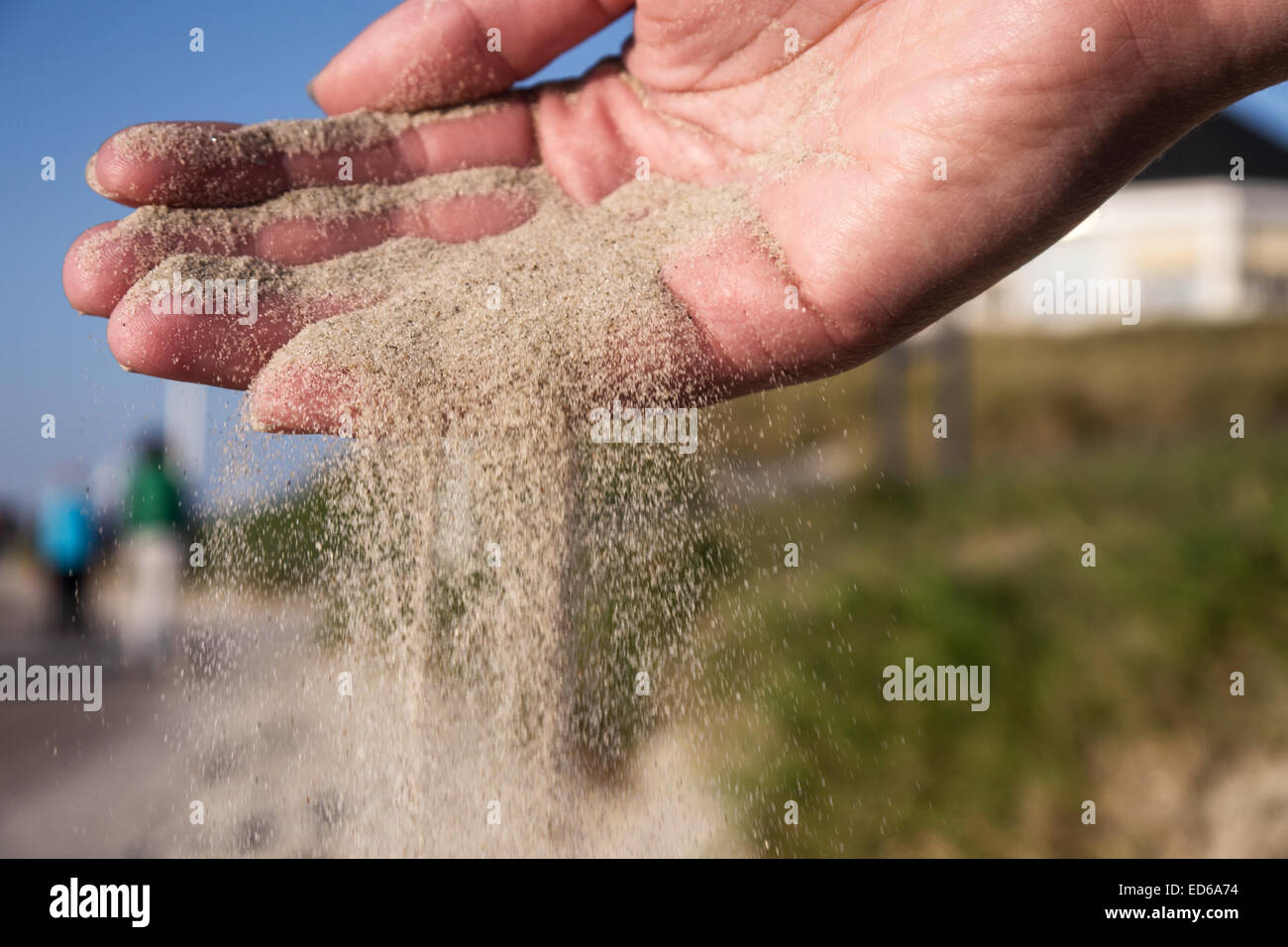Sand running through hands on beach - Stock Image