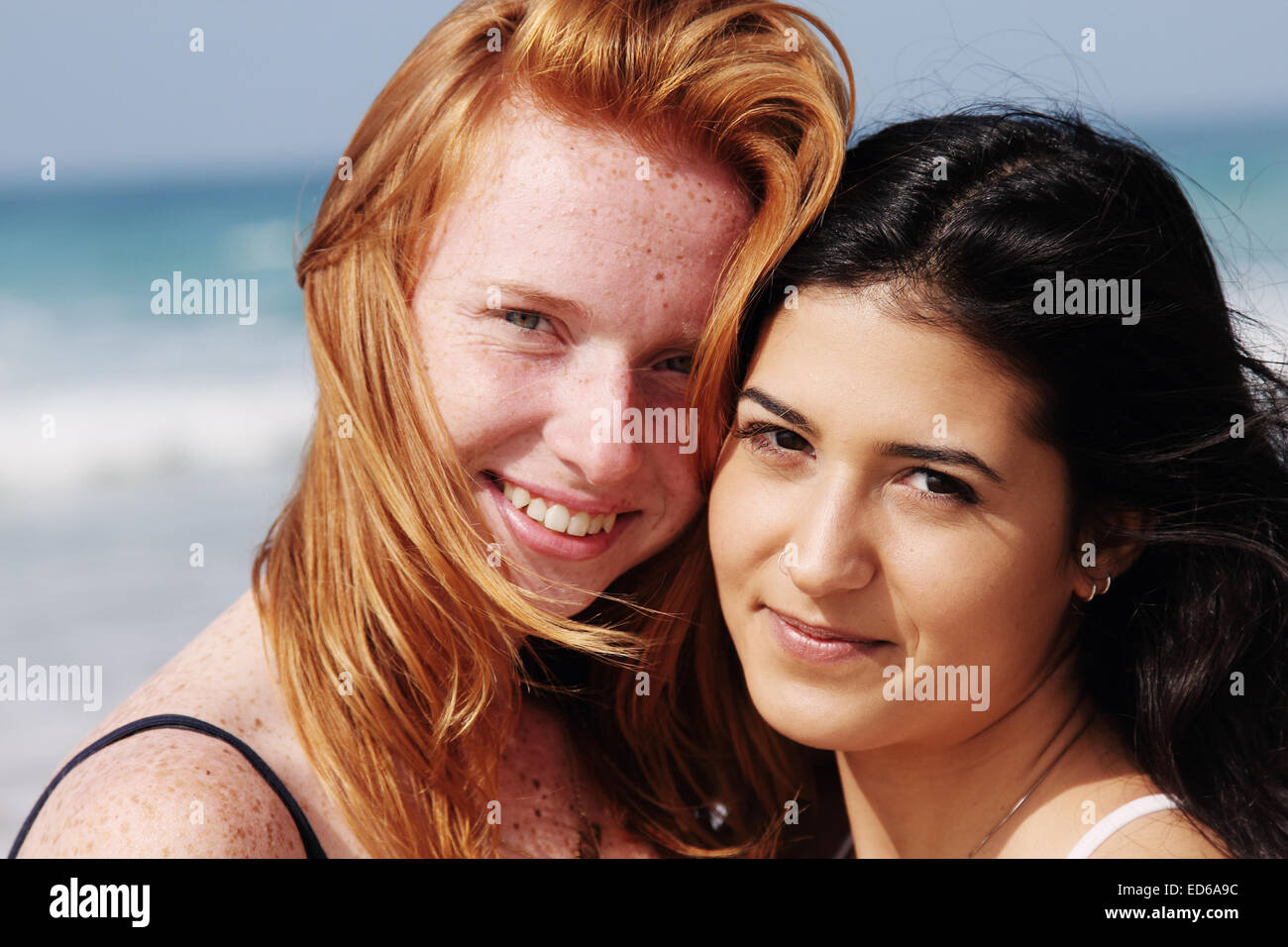 two smiling young teenage girlfriends on the beach - Stock Image