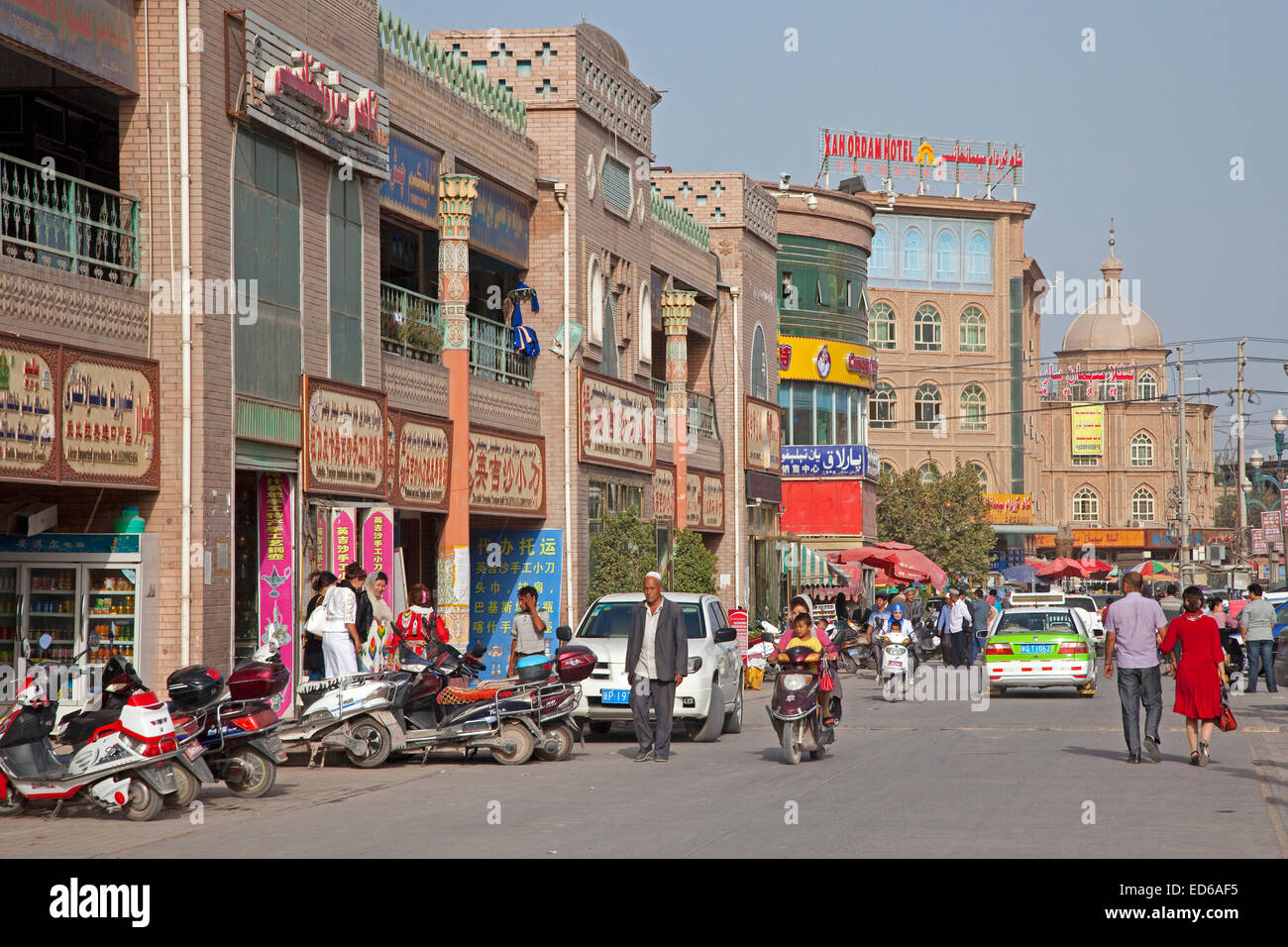Scooters in busy shopping street in the city Kashgar / Kashi, Xinjiang Province, China - Stock Image
