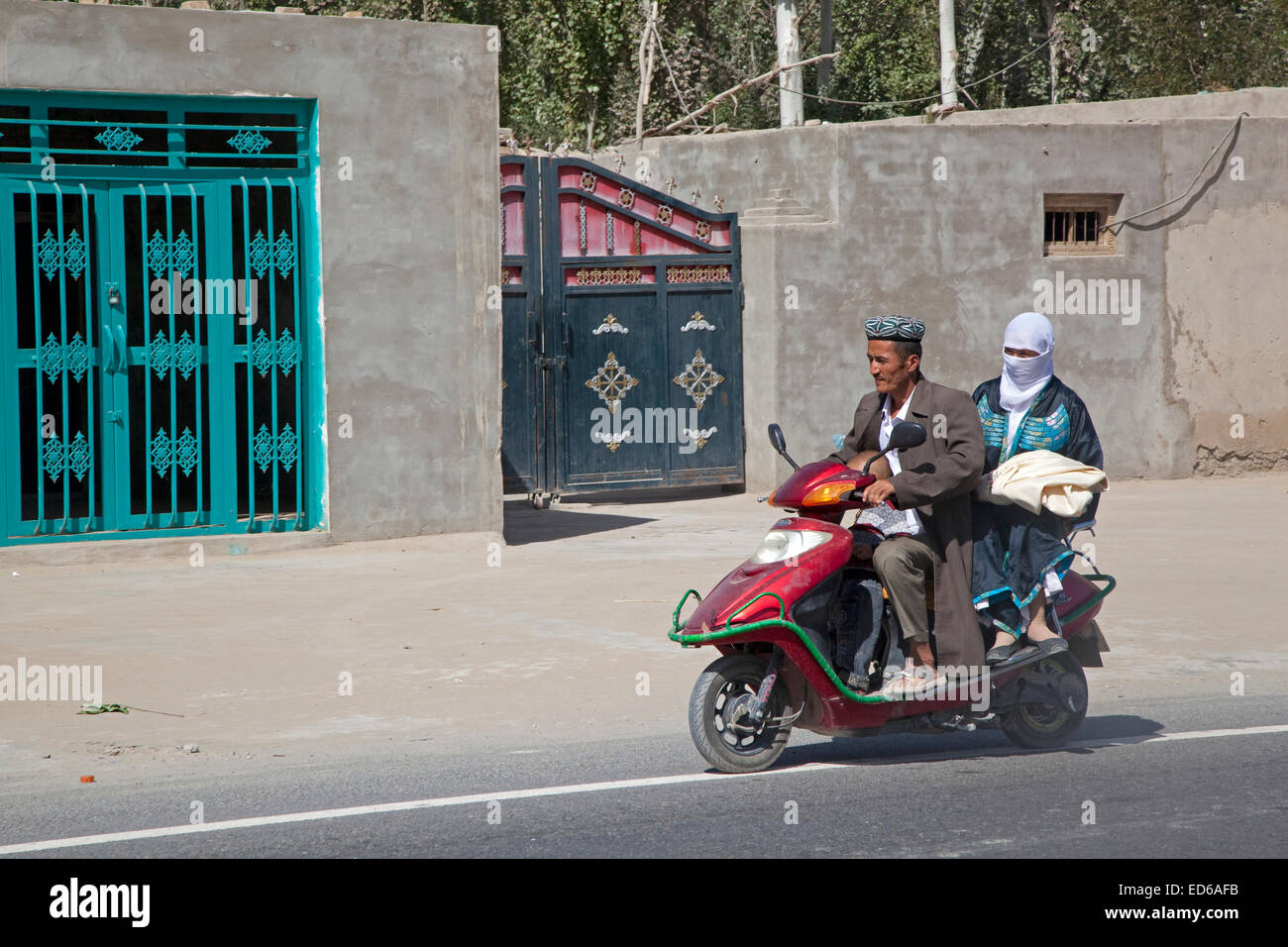 Uyghur man in traditional muslim dress, child and wife wearing Islamic veil riding on a scooter, Xinjiang Province, - Stock Image