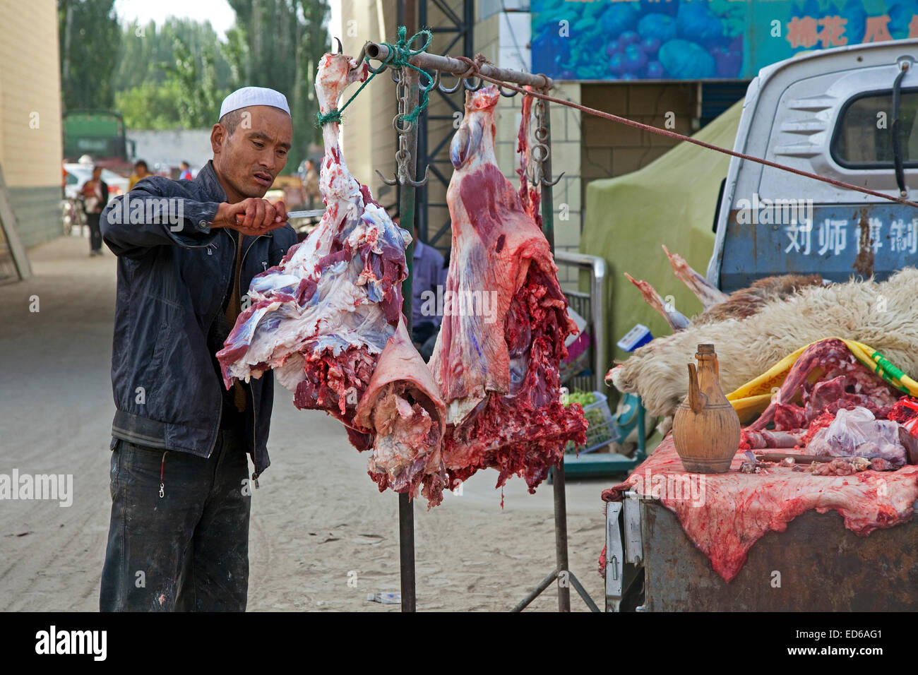 Butcher cutting meat from his pickup truck in the village Waxxari, oasis town in the Taklamakan Desert, Xinjiang - Stock Image