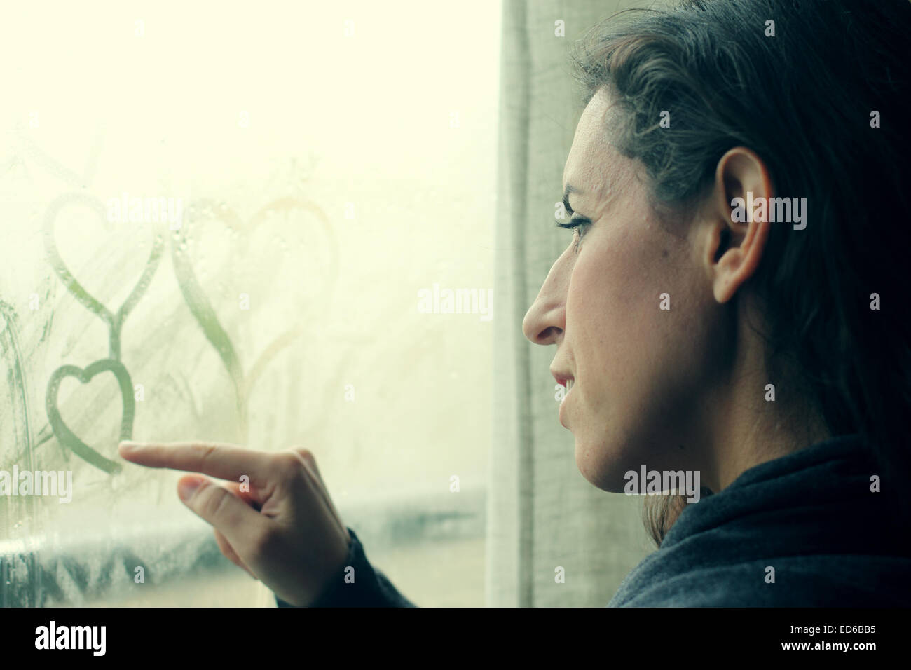 mid adult woman looking out of the window - Stock Image