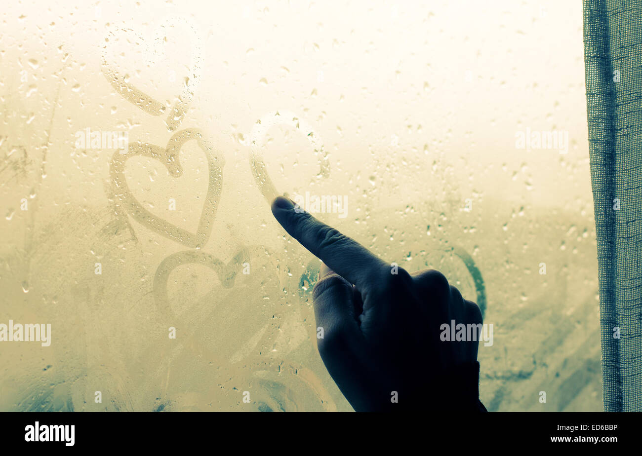 woman drawing heart on wet window Stock Photo