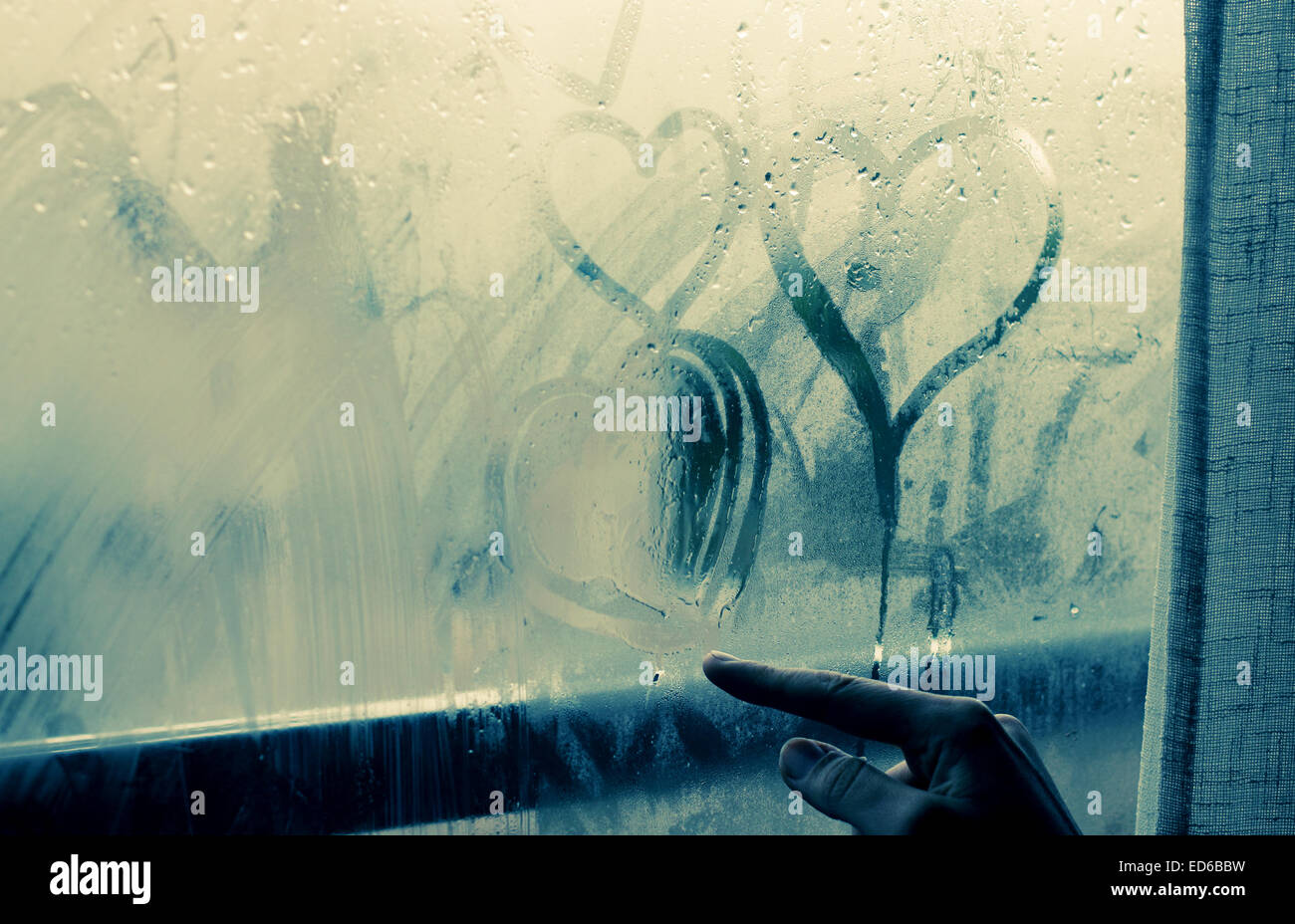 woman drawing heart on wet window Stock Photo