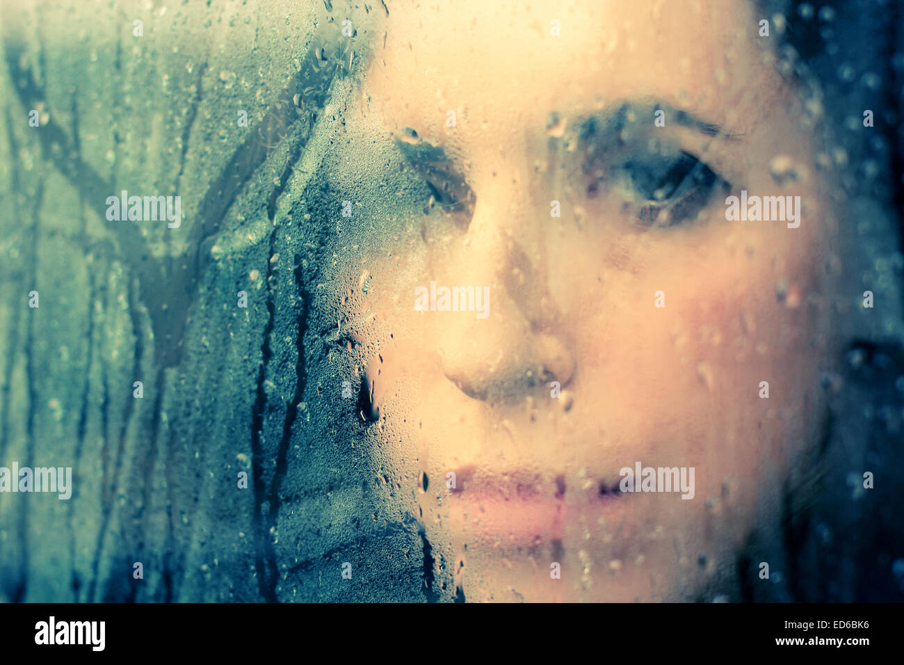 beautiful 35 year old woman stands in front of the window - Stock Image
