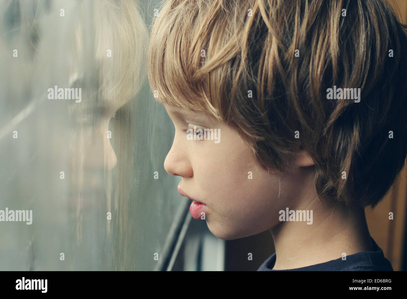 Cute 6 years old boy looking through the window - Stock Image