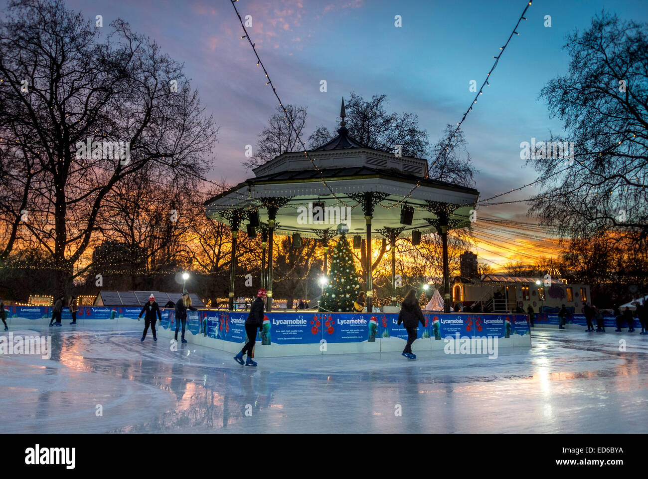 Skaters on ice rink around bandstand in Hyde Park at Winter Wonderland - Stock Image