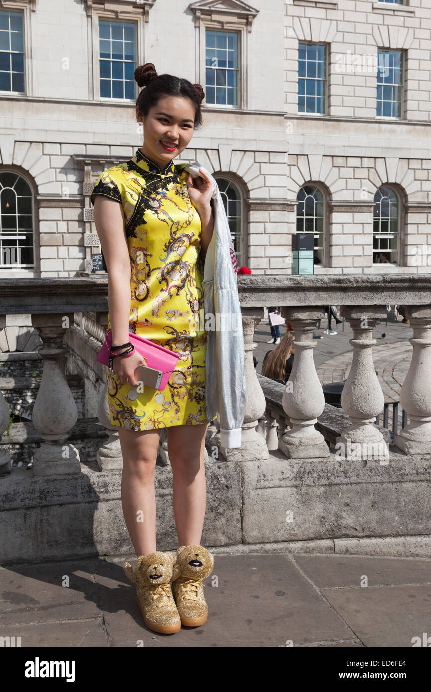 f988d0812 A young woman in a Chinese dress and golden teddy bear trainers presents  her street style fashion at London Fashion Week.