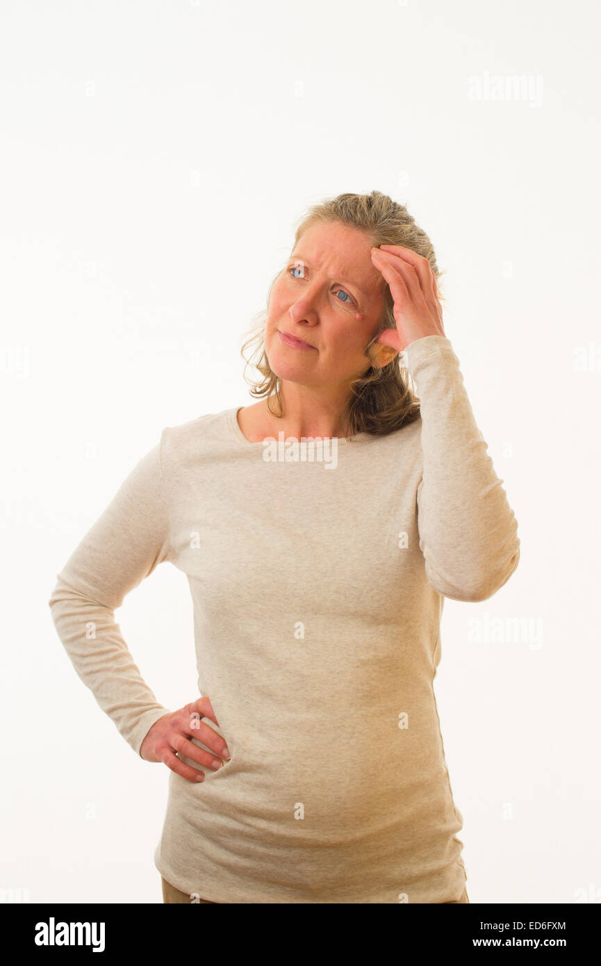 A confused uncertain unsure worried  forty year old caucasian woman scratching her head against a white background. - Stock Image