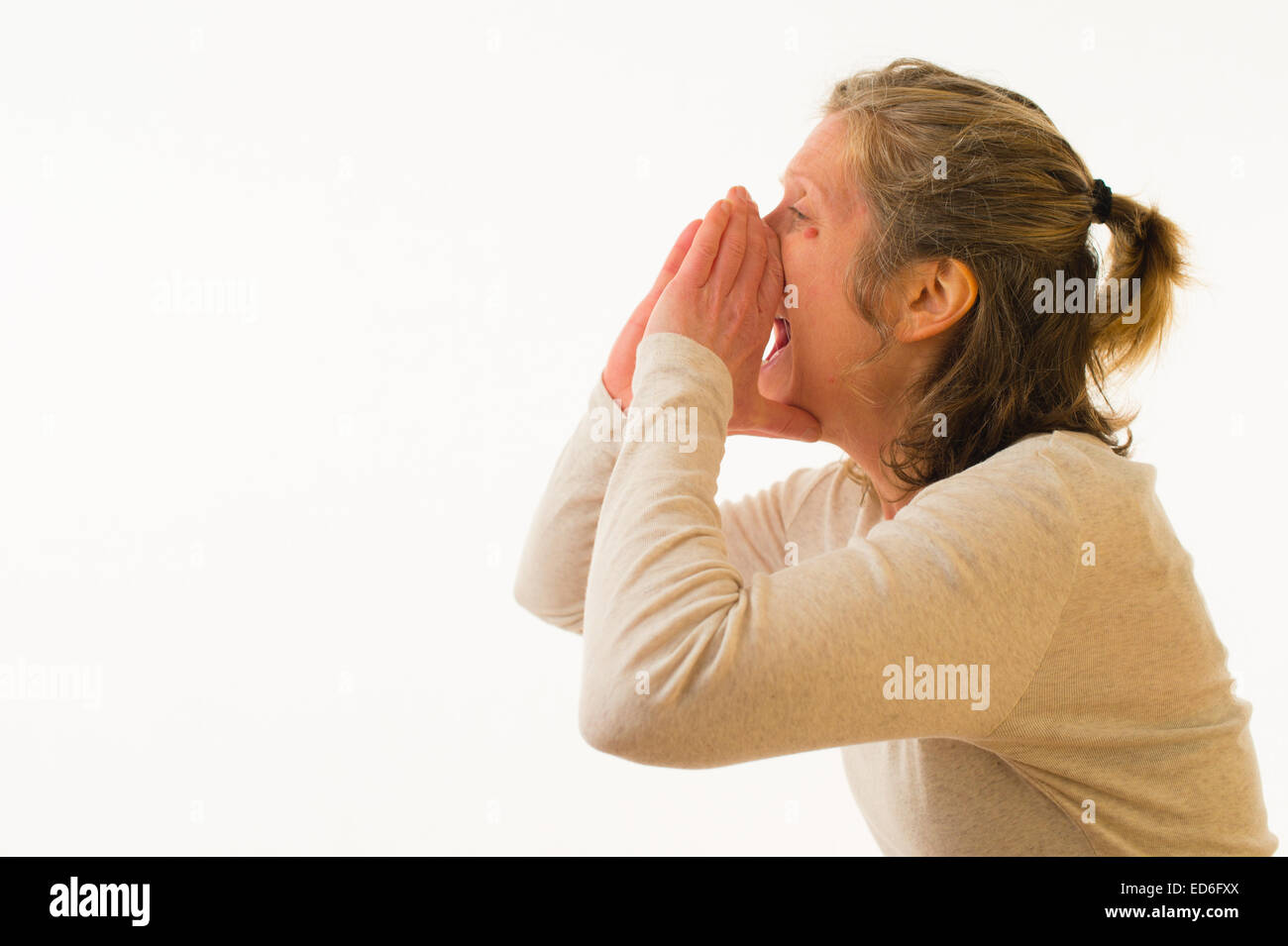 A forty year old caucasian woman shouting yelling through her cupped hands against a white background. UK - Stock Image