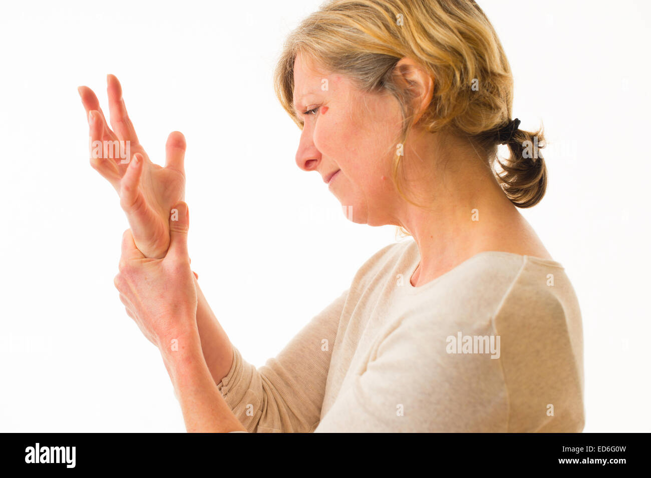 A forty year old caucasian woman with painful arthritis in the joints of her hand wrist and fingers, rubbing her - Stock Image