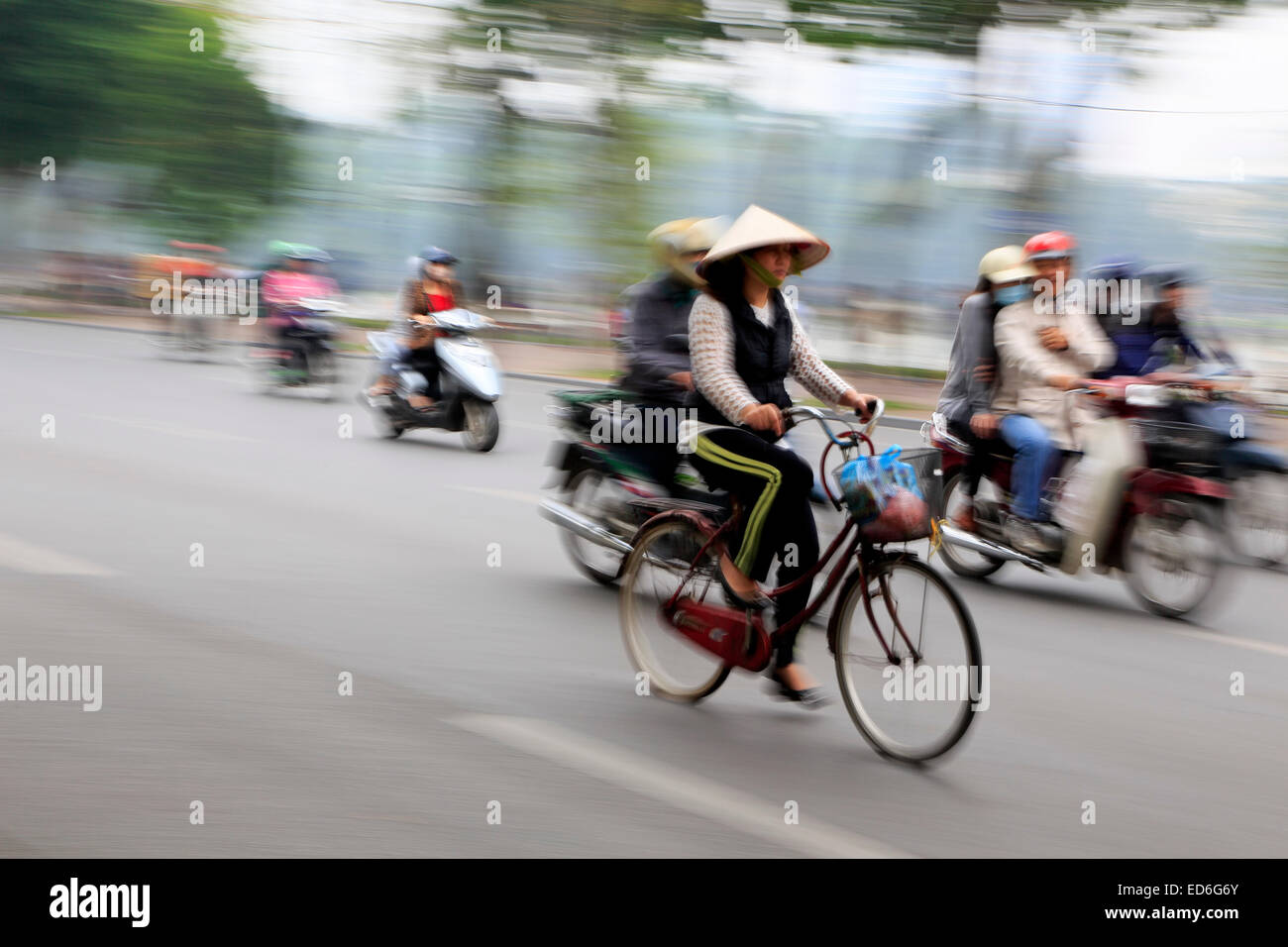 Woman on bike and scooters buzzing by, Hanoi, Vietnam - Stock Image