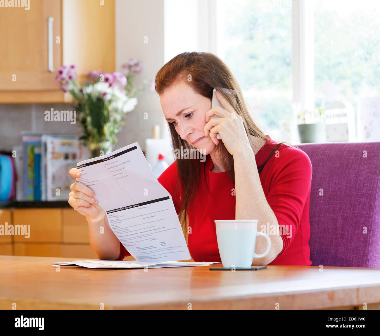 woman worried about credit card bills / bank statement - Stock Image