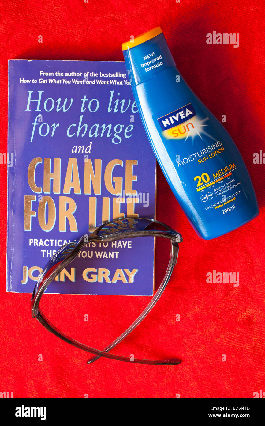 How to live for change and change for life book, sunglasses and Nivea Sun suntan lotion on orange towel - Stock Image
