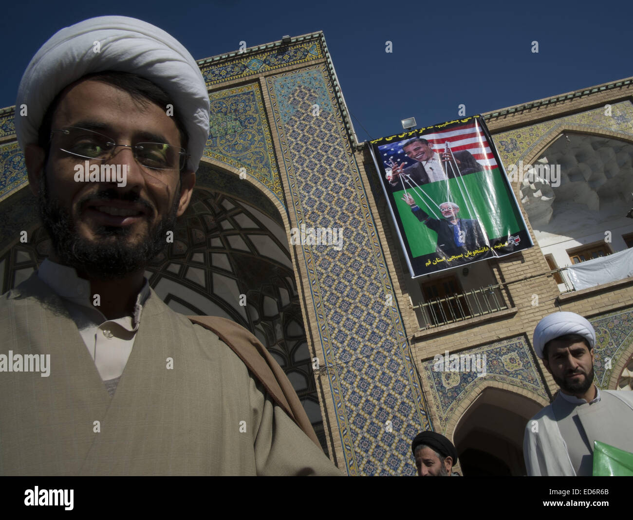 Qom, Iran. 29th Dec, 2014. December 30, 2014 - Qom, Iran - Two Iranian clerics look on as a banner with images of - Stock Image