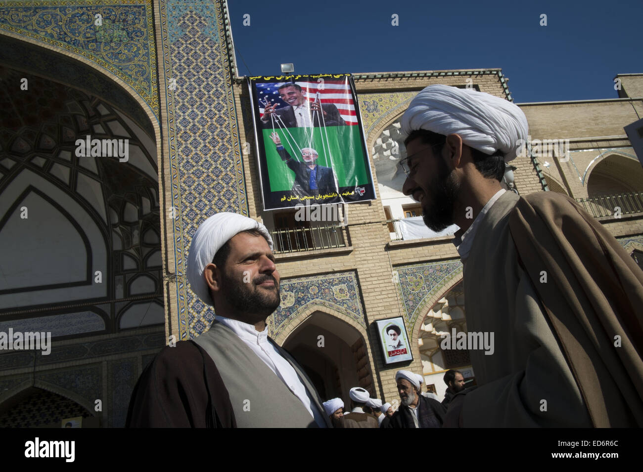 Qom, Iran. 29th Dec, 2014. December 30, 2014 - Qom, Iran - Two Iranian clerics talk with each other as a banner - Stock Image