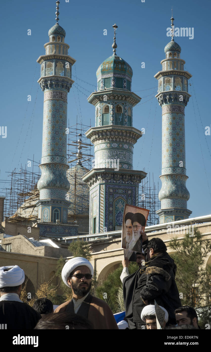 Qom, Iran. 30th Dec, 2014. December 30, 2014 - Qom, Iran - An Iranian man holds-up a poster with portraits of Iran's - Stock Image