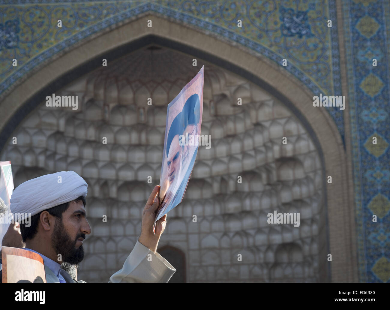 Qom, Iran. 30th Dec, 2014. December 30, 2014 - Qom, Iran - An Iranian cleric holds a poster with portraits of Iran's - Stock Image
