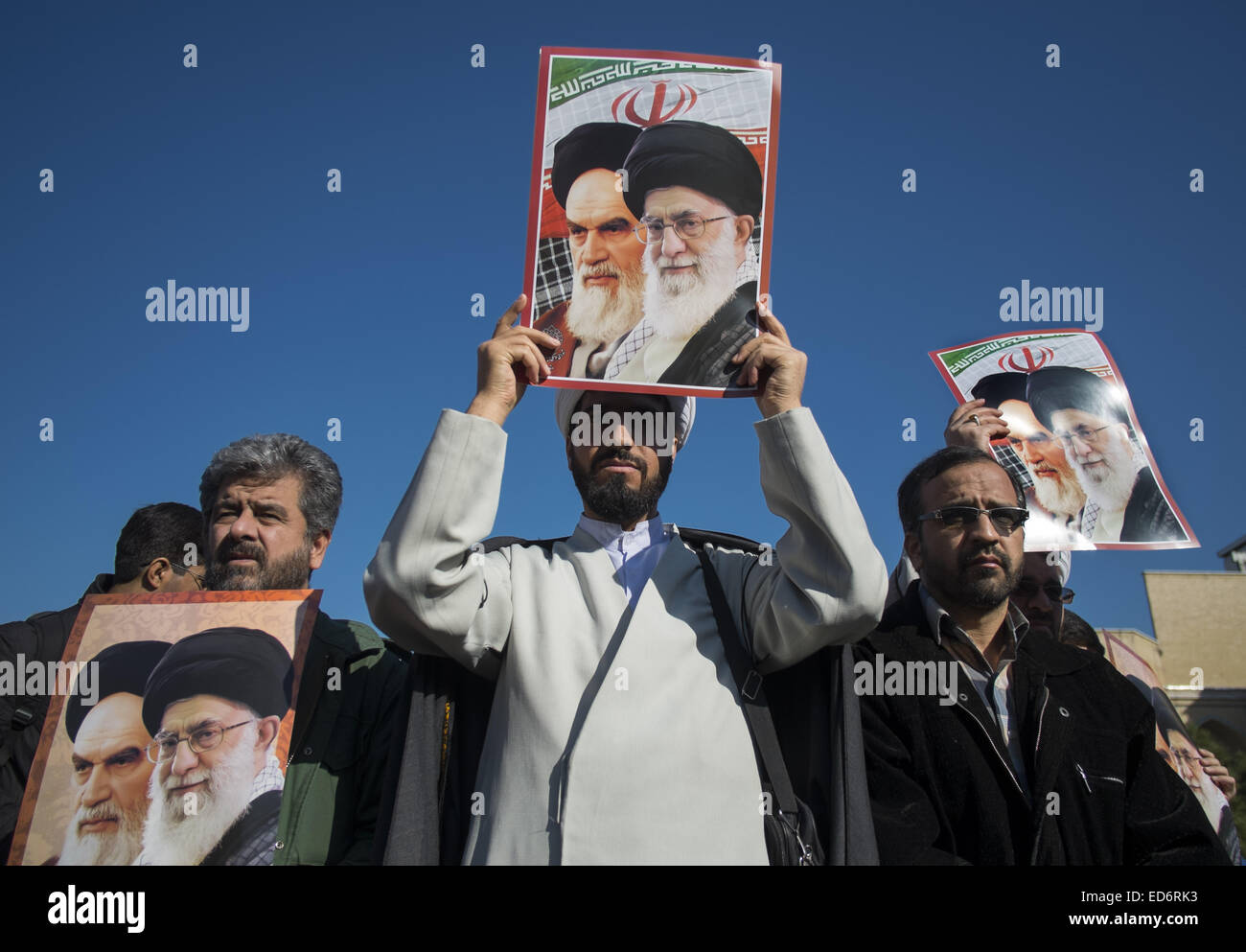 Qom, Iran. 29th Dec, 2014. December 30, 2014 - Qom, Iran - An Iranian cleric and men hold posters with portraits - Stock Image