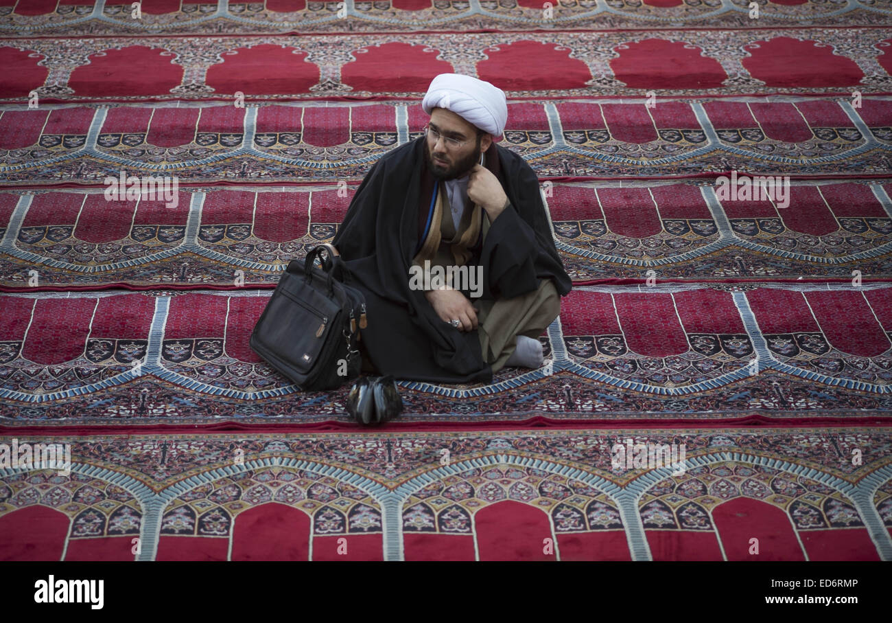 Qom, Iran. 30th Dec, 2014. An Iranian cleric looks on as he sit at faziye Seminary in the holy city of Qom 120 km - Stock Image
