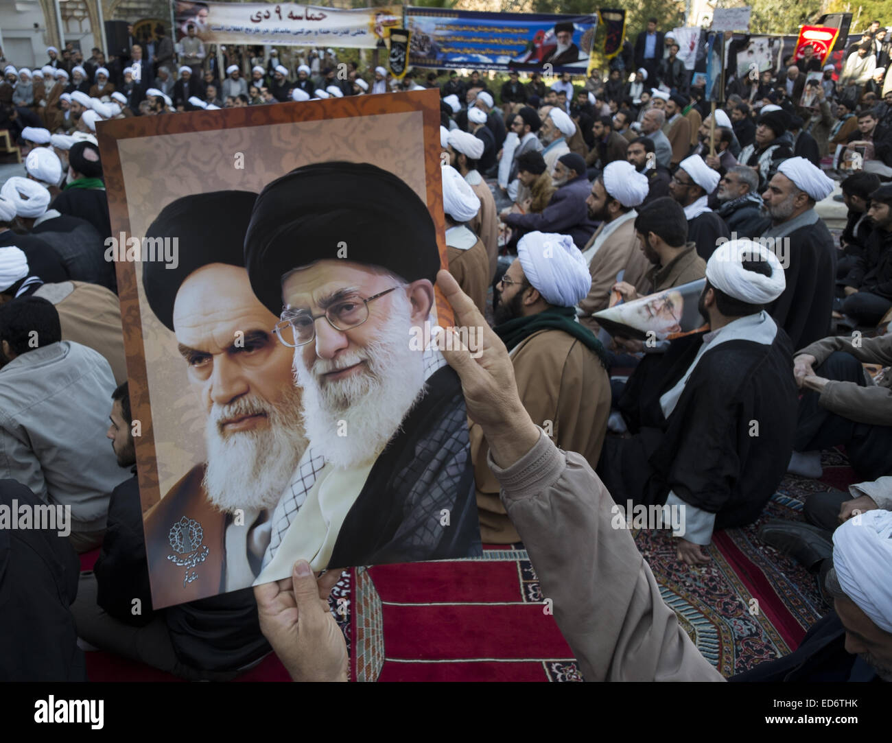 Qom, Iran. 30th Dec, 2014. An Iranian cleric and other men hold posters with portraits of Iran's Supreme Leader - Stock Image