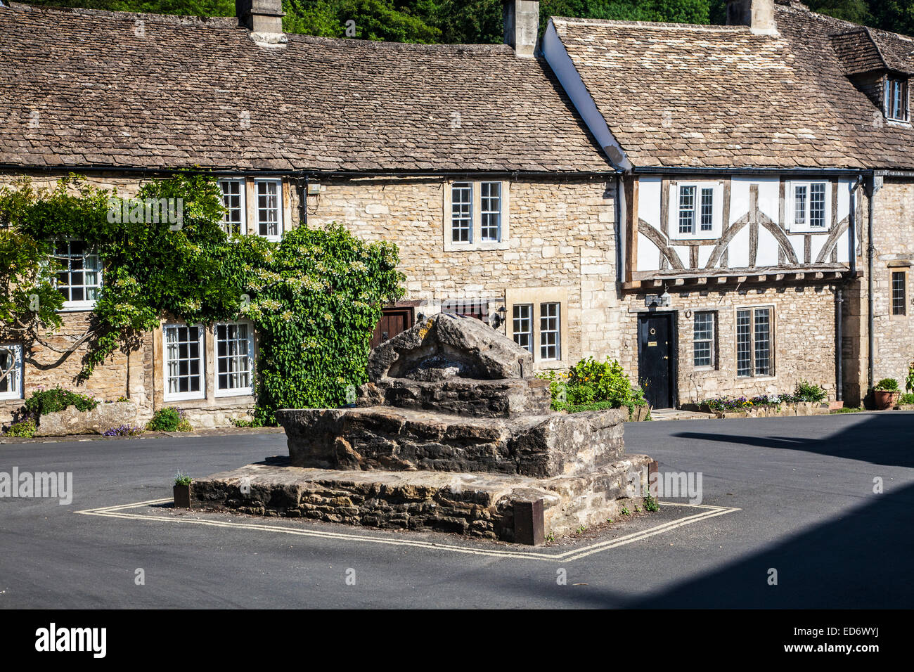 The half-timbered Court House in the Cotswold village of Castle Combe in Wiltshire with the remains of the buttercross - Stock Image