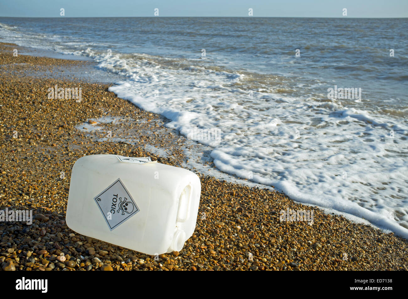 Plastic container with Toxic sticker, washed up on the North Sea beach, Bawdsey Ferry, Suffolk, UK. - Stock Image