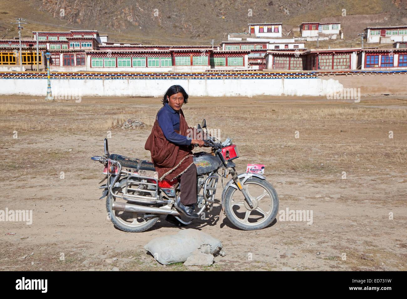Tibetan man riding motorbike in front of monastery between Sershu Dzong and Sershu / Serxu, Sichuan Province, China - Stock Image