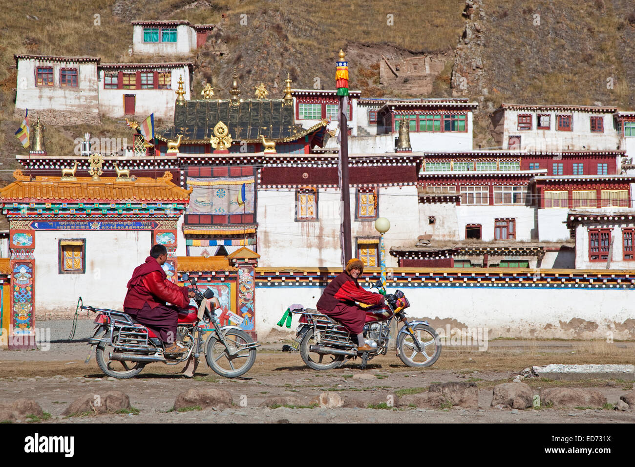 Two young Tibetan monks riding motorbikes in front of monastery between Sershu Dzong and Sershu / Serxu, Sichuan - Stock Image