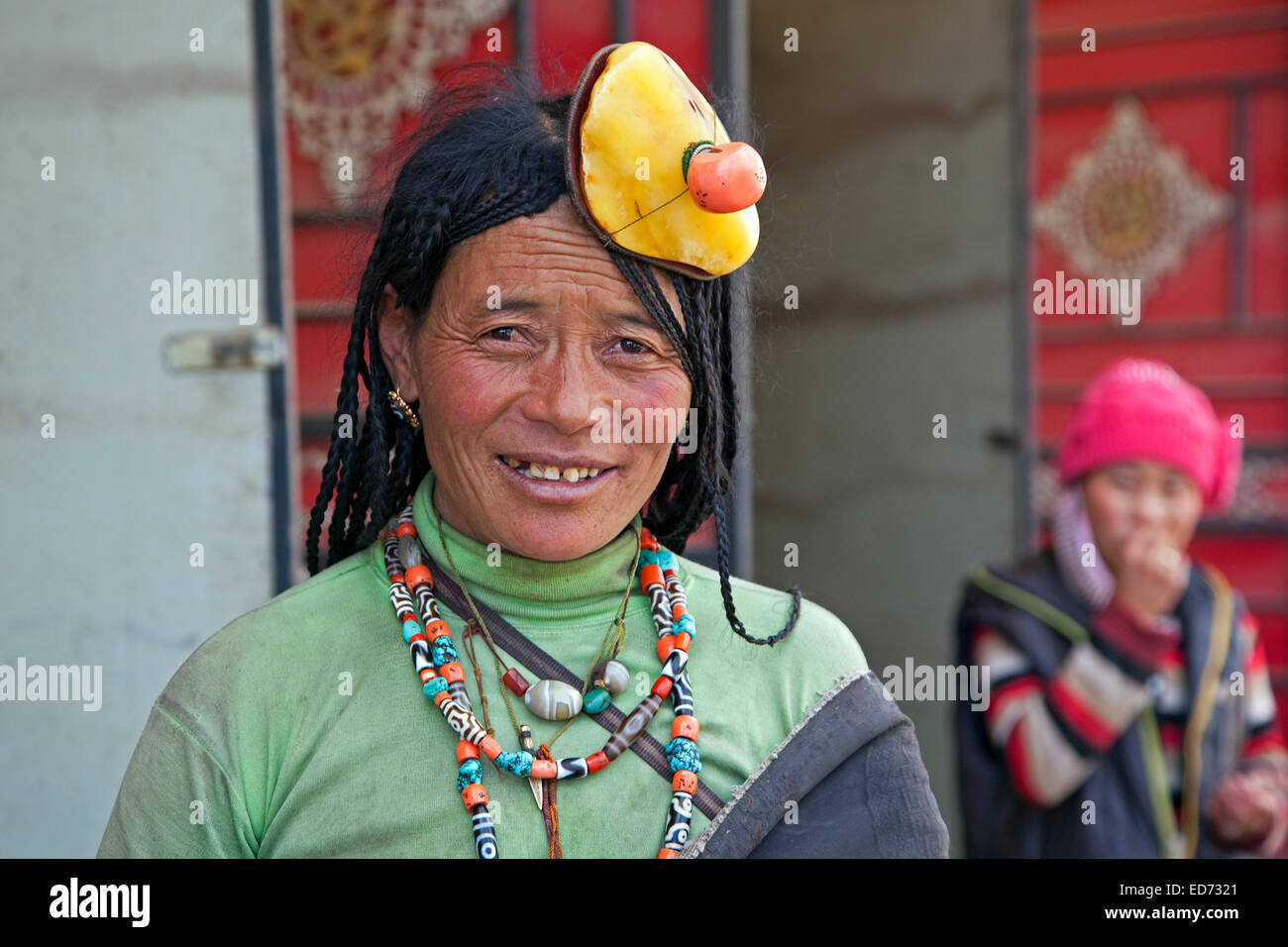 Portrait of Tibetan Khampa woman wearing traditional amber and red coral hair piece at Zhuqing, Sichuan Province, - Stock Image