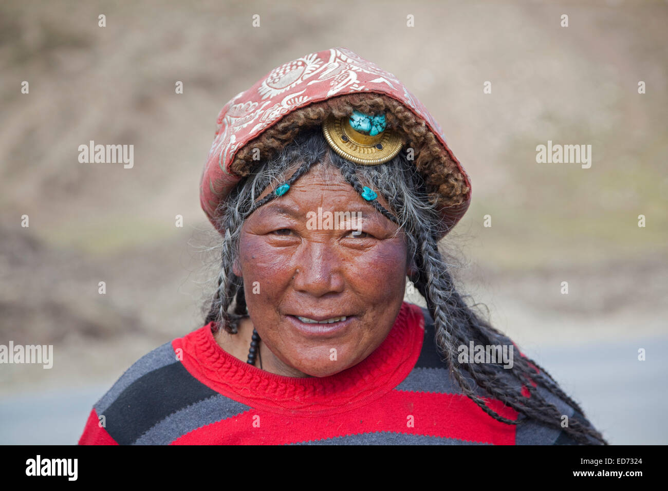 Portrait of Tibetan Khampa woman wearing traditional amber hair piece at Zhuqing, Sichuan Province, China - Stock Image