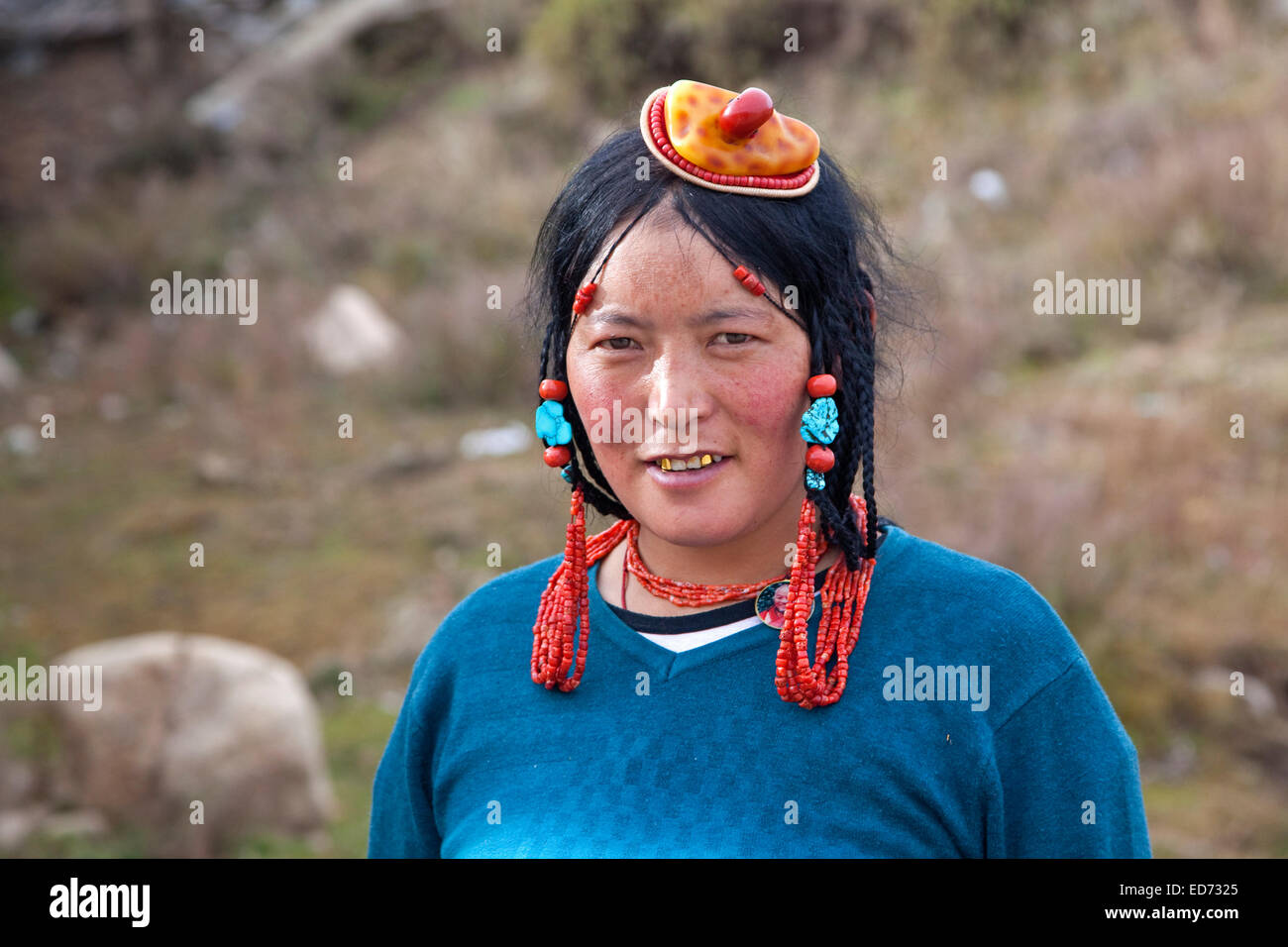 Portrait of Tibetan Khampa woman wearing jewelry, traditional amber and red coral hair piece at Zhuqing, Sichuan - Stock Image