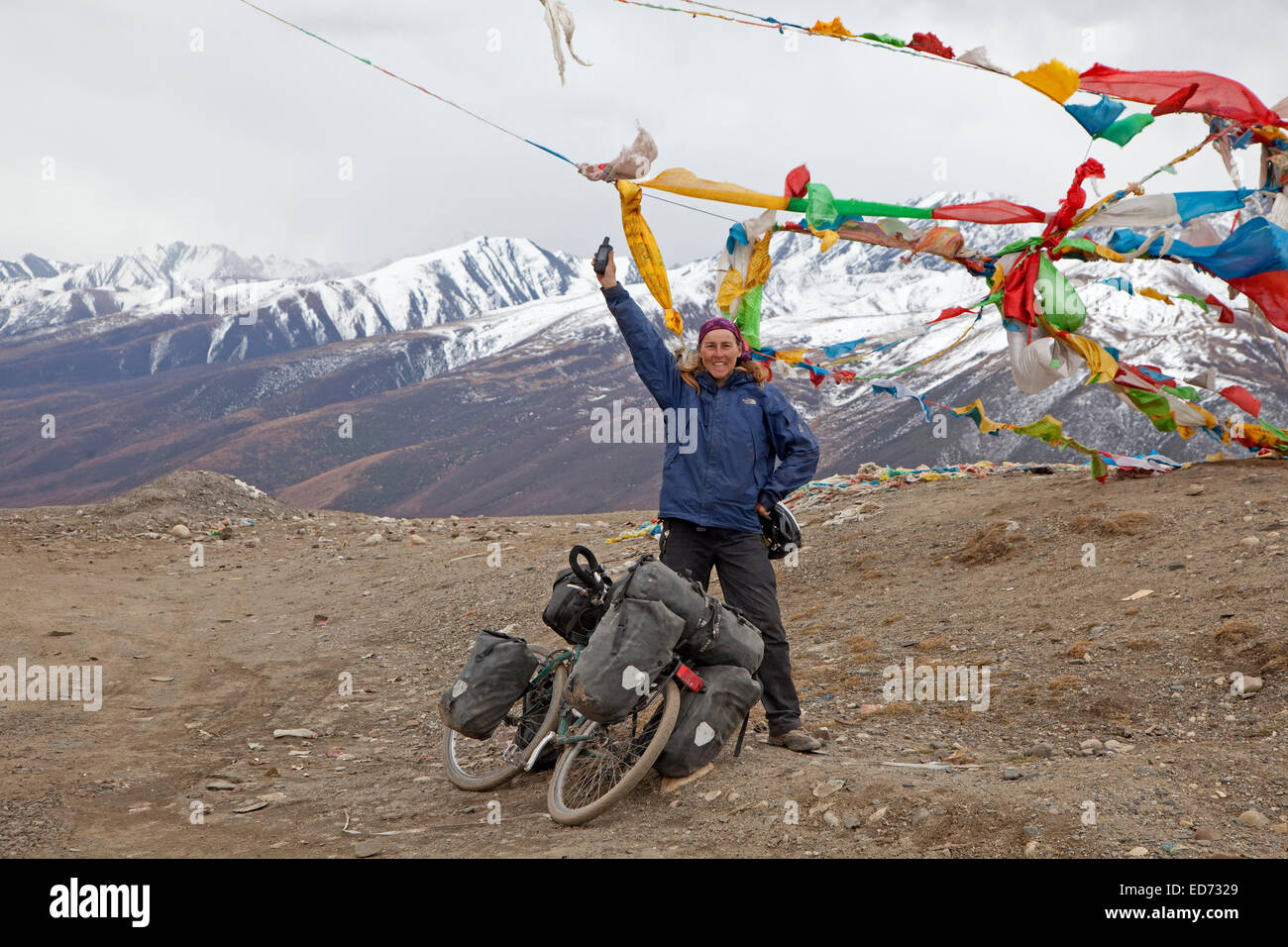 Proud female trekking cyclist conquered 4500 meter high mountain pass in Himalayas on the Sichuan-Tibet Highway, - Stock Image