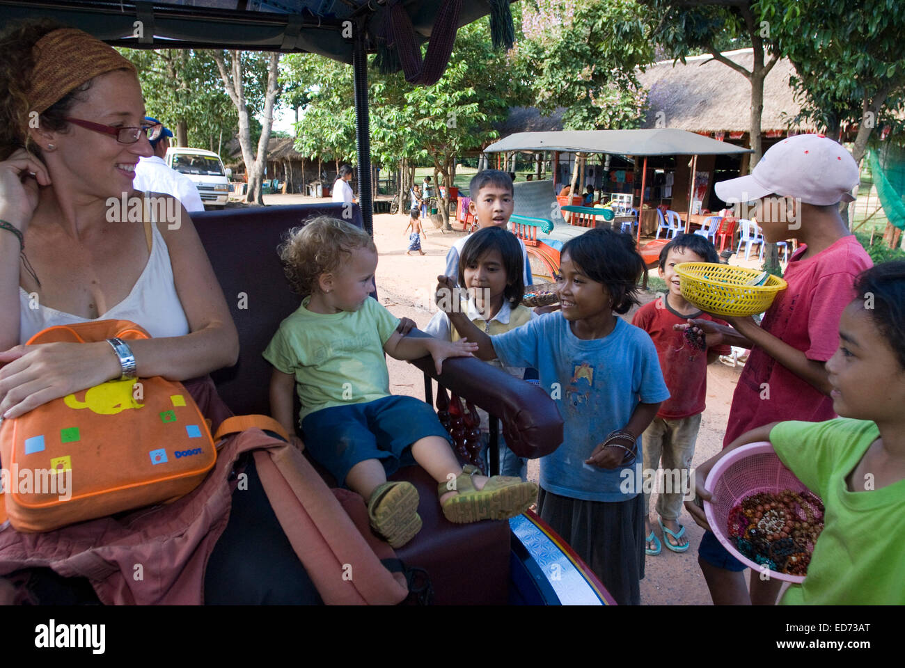 Travel with children's. Boys selling postcards and souvenirs to a mother walking with her daughter. Preah Khan Temple. - Stock Image