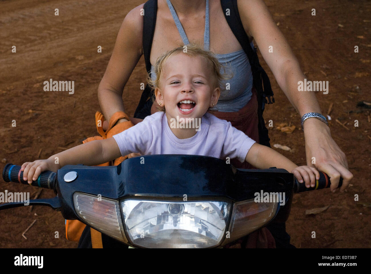 Travel with children's. Mother riding a motorbike with her daughter. Ratanakiri. The protected area of Yeak Lom - Stock Image