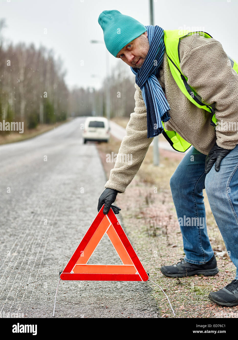 Mid adult man wearing reflector vest and he have a red warning triangle - road and vehicle on background - Stock Image
